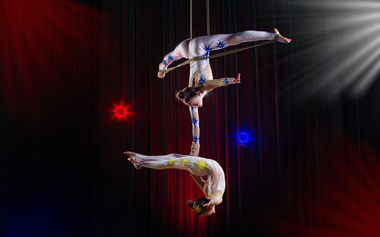 Two girls perform acrobatic elements in the air.