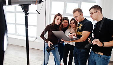 A male photographer teacher teaching 4 students in a photography studio while holding a laptop