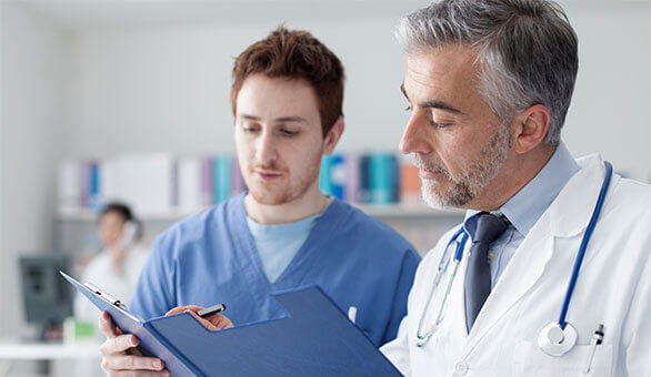 medical assistant looking at a file with a doctor