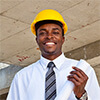 Male engineer wearing a hard hat and holding a rolled blueprint in a construction site