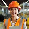 Portrait of a female engineer wearing a hard hat and holding a tablet at a factory